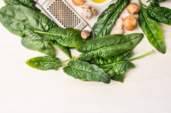 Espinaca fresca con el rallador de la nuez moscada moscada, la cebolla y el ajo viejos, ingredientes Foto de archivo