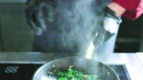 Espinafres da fritura com cebola em um frigideira filme