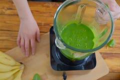 Espinafres da mulher, bananas e leite de mistura da amêndoa para fazer um batido verde saudável fotos de stock royalty free