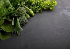 - espinafres, pepino, brócolis, alho, hortelã, salsa, alface, cebola em um fundo preto Foto de Stock