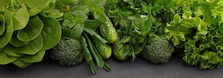 - espinafres, pepino, brócolis, alho, hortelã, salsa, alface, cebola em um fundo preto Imagem de Stock Royalty Free