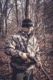 Espingarda da carga do homem do caçador durante a caça na floresta do outono com árvores e as folhas secas foto de stock