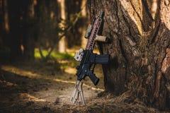Espingarda de assalto no fundo da floresta Imagens de Stock Royalty Free