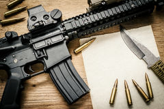 Espingarda de assalto, papel e balas na tabela Fotos de Stock