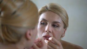 Espinha de estalo da senhora bonita incerta na pele, examinando sua reflexão de espelho filme