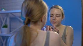 Espinilla femenina de la cara de la universidad que hace estallar que mira el espejo, higiene personal, dermatología metrajes