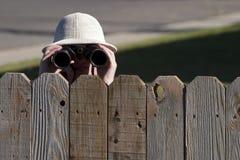 Espionaje sobre la cerca con los prismáticos Imágenes de archivo libres de regalías