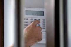 Espionnage d'un homme armant un système d'alarme de cambrioleur Images stock