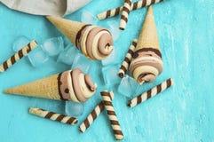 Espirais cremosas do gelado do chocolate e do caramelo em cones do waffle Foto de Stock