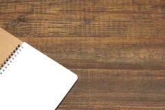 Espiral abierto - cuaderno encuadernado con white pages en el fondo de madera Foto de archivo