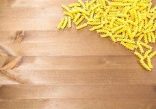 Espirales de los macarrones dispersados en una tabla de madera Foto de archivo