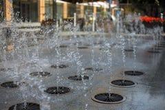 Espirra da água de uma fonte no verão na cidade foto de stock