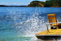 Espirra das ondas deixando de funcionar no lado do catamarã amarelo, estando na praia do acampamento do turista foto de stock royalty free