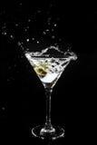 Espirrando a azeitona em um vidro de martini Foto de Stock