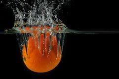 Espirrando a laranja em uma água fotografia de stock royalty free