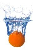 Espirrando a laranja em uma água imagem de stock
