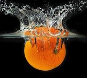 Espirrando a laranja em uma água foto de stock royalty free