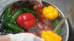 Espirrando o água da torneira em vegetais filme