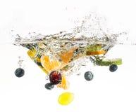 Espirrando o fruto na água. Fotografia de Stock