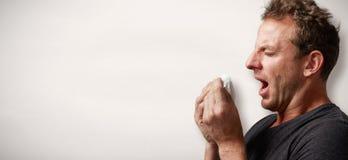 Espirrando o homem com frio foto de stock