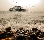Espirrando o oceano e o cais abandonado fotos de stock