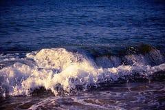 Espirrando a onda no mar na noite, foto de stock