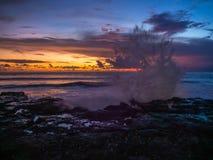 Espirrando ondas das pedras no fundo de nuvens multi-coloridas no por do sol imagem de stock