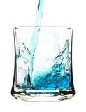 Espirre, bebida azul está sendo derramado no vidro Fotografia de Stock