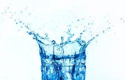 Espirro da água azul isolado no fundo branco. Fotografia de Stock