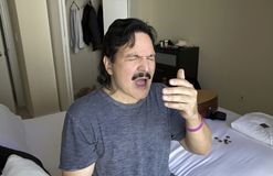Espirros do homem ao sentar-se na cama Fotografia de Stock