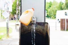 Espita del agua en un manantial artesiano que fluye Dos damajuanas plásticas Imagen de archivo