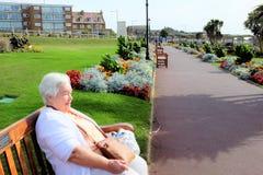Esplanade gardens, Hunstanton, Norfolk. Hunstanton, Norfolk, UK. September 18, 2018. A senior holidaymaker relaxing and enjoying the colors of the Esplanade royalty free stock photography