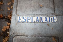 Esplanade place name set into a concrete sidewalk. Esplanade place in blue and white letters name set into a concrete sidewalk with fallen dead brown autumn Royalty Free Stock Photography