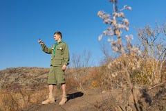 Esploratore che sta su una roccia che annota una lettura della bussola Fotografia Stock Libera da Diritti