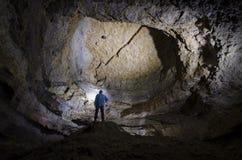 Esploratore dell'uomo in caverna enorme sotterranea Fotografia Stock