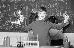 Esplori le molecole biologiche Concetto futuro di scienza e di tecnologia Microscopio della tenuta del ragazzo e provetta a scuol fotografia stock