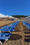 Esponga al sole i letti e gli ombrelli su una spiaggia sabbiosa Immagine Stock