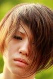 Esponga al sole il ritratto di un Coreano afflitto, mèche del fronte della copertura dei capelli Fotografie Stock Libere da Diritti