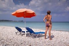Esponga al sole la chaise-lounge e l'ombrello sulla spiaggia sabbiosa vuota Fotografia Stock Libera da Diritti