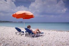 Esponga al sole la chaise-lounge e l'ombrello sulla spiaggia sabbiosa vuota Immagine Stock Libera da Diritti