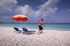 Esponga al sole la chaise-lounge e l'ombrello sulla spiaggia sabbiosa vuota Immagini Stock Libere da Diritti