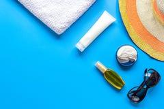 Esponga al sole la composizione nella protezione con i vetri e la crema sul modello blu di vista superiore del fondo Immagini Stock