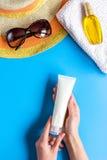 Esponga al sole la composizione nella protezione con i vetri e la crema sulla vista superiore del fondo blu Fotografie Stock Libere da Diritti