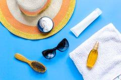 Esponga al sole la composizione nella protezione con i vetri e la crema sulla vista superiore del fondo blu Immagine Stock