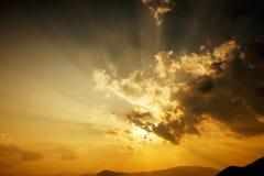Esponga al sole la regolazione dietro le nuvole e una siluetta delle montagne al crepuscolo Fotografie Stock Libere da Diritti