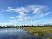 Esponga al sole la regolazione dietro le nuvole dietro un pilastro di legno su un lago Immagine Stock