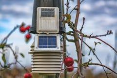 Esponga al sole la stazione alimentata della meteorologia sulle piante della mela immagini stock