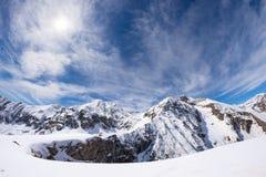 Esponga al sole la stella che emette luce sopra la catena montuosa snowcapped, alpi italiane Immagini Stock Libere da Diritti