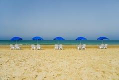 Esponga al sole le chaise-lounge e un ombrello di spiaggia su una spiaggia abbandonata Fotografia Stock
