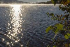 Esponga al sole le riflessioni in acqua un la mattina in anticipo di autunno con il leavin della nebbia fotografia stock